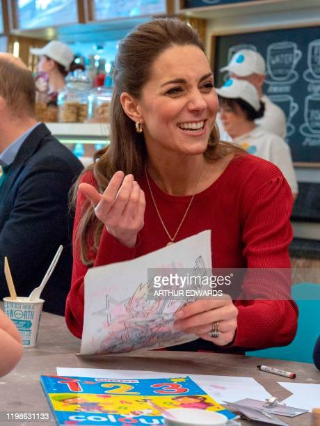 Britain's Catherine Duchess of Cambridge smiles as she meets with local parents and carers during her visit with her husband Britain's Prince William...