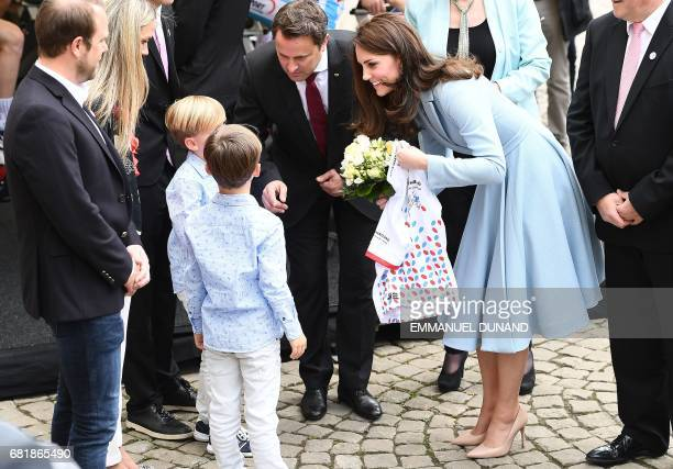 Britain's Catherine Duchess of Cambridge smiles as she receives a Luxembourg's cycling jersey next to Luxembourg's Prime Minister Xavier Bettel...