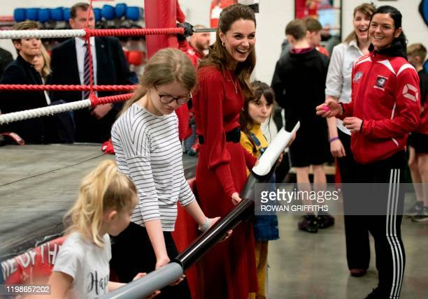Britain's Catherine Duchess of Cambridge smiles as she takes part in a group activity during a visit with her husband Britain's Prince William Duke...