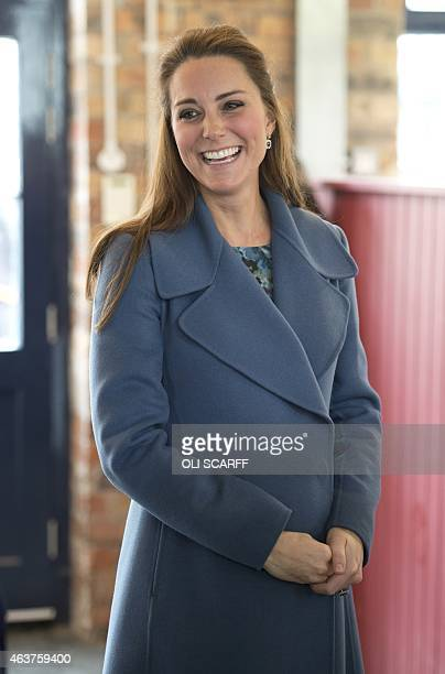 Britain's Catherine Duchess of Cambridge smiles as she visits the 'Emma Bridgewater' pottery factory to view the production of a mug that the company...