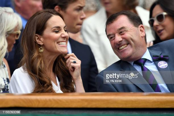 Britain's Catherine Duchess of Cambridge smiles with chairman of AELTC Philip Brook in the Royal Box on Centre Court watching Germany's Tatjana Maria...