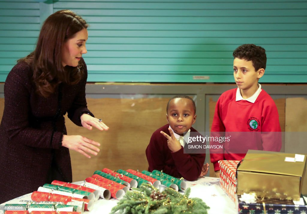 Britain's Catherine, Duchess of Cambridge speaks to Yahya Hussein Ali, 7, (C) and Dawud Wahabi, 10, (R), who were affected by the Grenfell Tower fire, during a visit to the Rugby Portobello Trust's Christmas party at its community centre in North Kensington, London on December 12, 2017. /