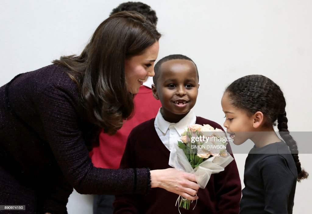 Britain's Catherine, Duchess of Cambridge speaks to Yahya Hussein Ali, 7, (CR), Dawud Wahabi, 10, (CL) and Ailise Taylor, 7, (R), who were affected by the Grenfell Tower fire, during a visit to the Rugby Portobello Trust's Christmas party at its community centre in North Kensington, London on December 12, 2017. /