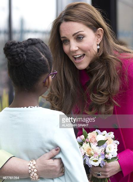 Britain's Catherine Duchess of Cambridge speaks with a girl after a visiting the Stephen Lawrence Centre on March 27 2015 in London The Stephen...