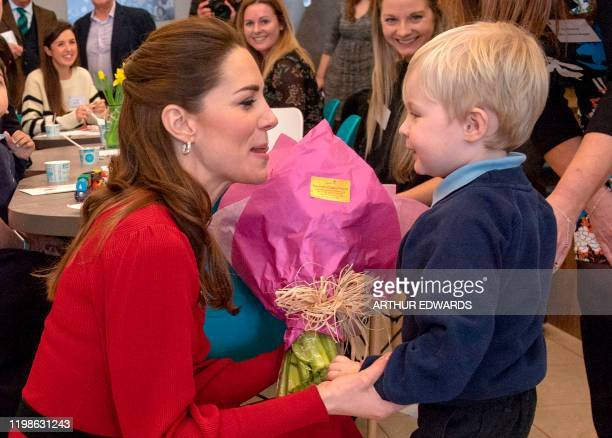 Britain's Catherine Duchess of Cambridge speaks with a young boy during a visit with her husband Britain's Prince William Duke of Cambridge to Joe's...