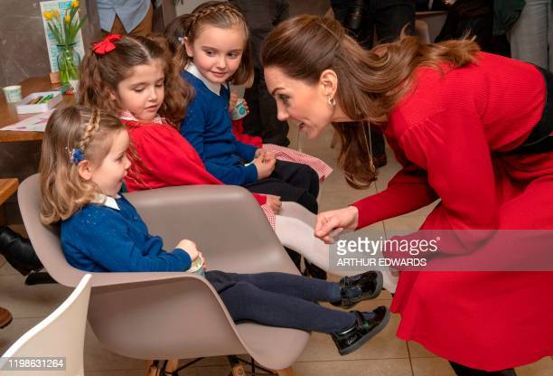 Britain's Catherine Duchess of Cambridge speaks with a young girl during a visit with her husband Britain's Prince William Duke of Cambridge to Joe's...