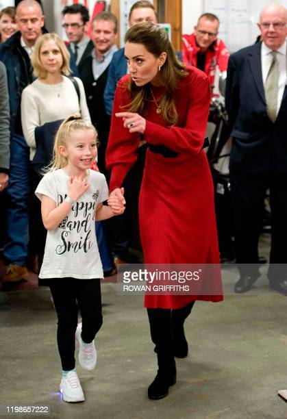 Britain's Catherine, Duchess of Cambridge speaks with a young girl during a visit with her husband Britain's Prince William, Duke of Cambridge to the...