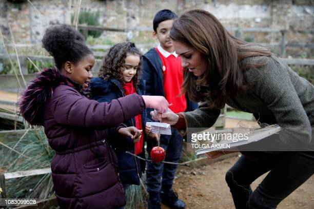 Britain's Catherine Duchess of Cambridge speaks with children as she visits the Islington community garden in north London on January 15 2019