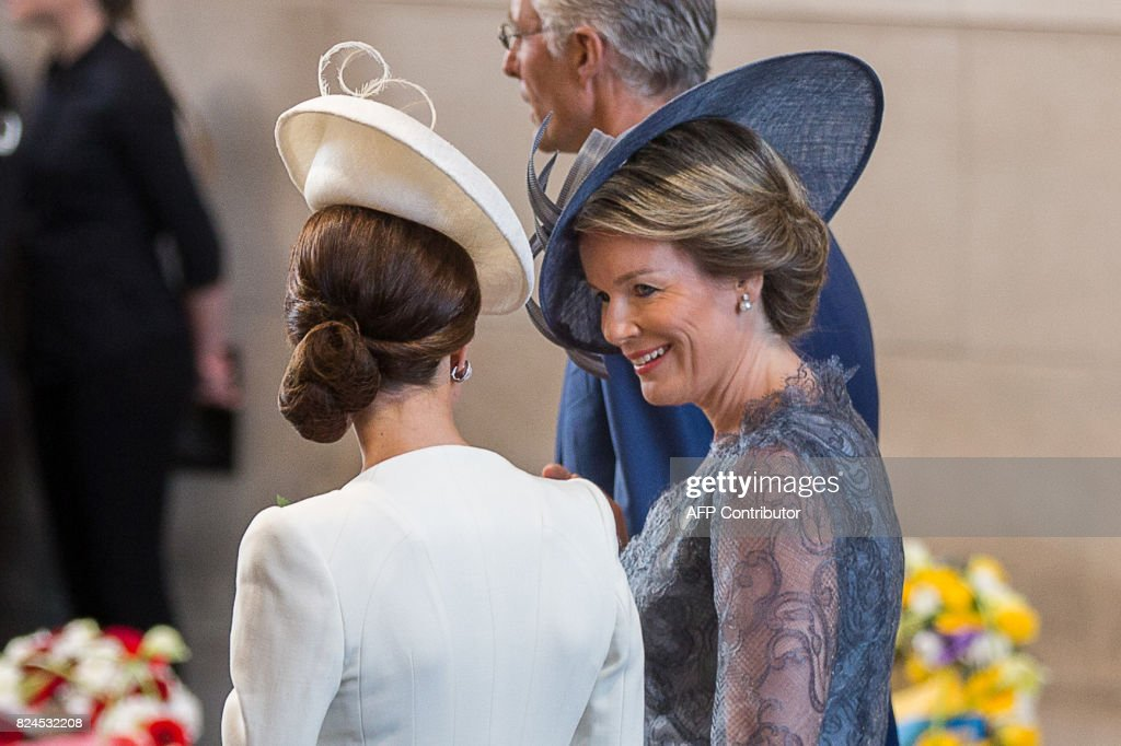 Britain's Catherine, Duchess of Cambridge, speaks with Queen Mathilde of Belgium (R) as they attend the Last Post ceremony at the Commonwealth War Graves Commission Ypres Memorial at the Menin Gate, Ypres, part of the commemoration for the centenary of Passchendaele, the third battle of Ypres, West Flanders on July 30, 2017. The battle of Passchendaele, also called the third battle of Ypres, took place between July 31 and November 6, 1917 in Passendale, West Flanders. / AFP PHOTO / POOL / Alain ROLLAND