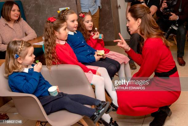 Britain's Catherine Duchess of Cambridge speaks with young girls during a visit with her husband Britain's Prince William Duke of Cambridge to Joe's...