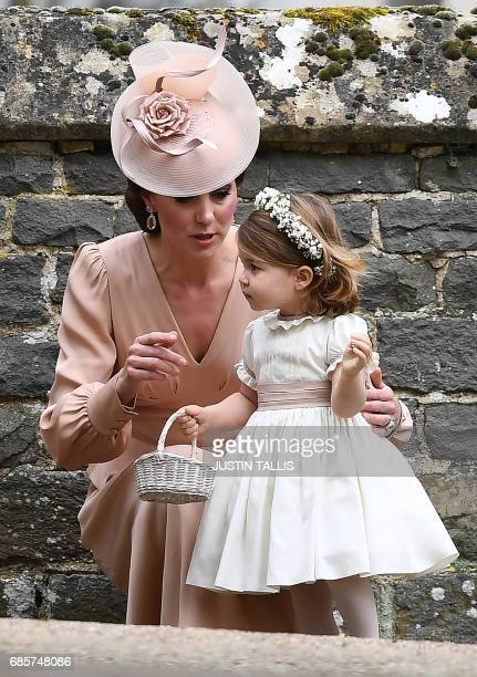 Britain's Catherine, Duchess of Cambridge stands with her daughter Britain's princess Charlotte, a bridesmaid, following the wedding of her sister...