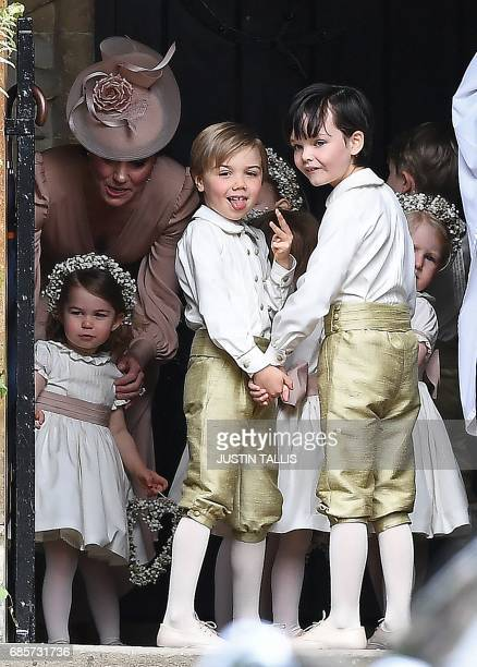 Britain's Catherine Duchess of Cambridge stands with her daughter Britain's princess Charlotte and the other bridesmaids and pageboys as they await...