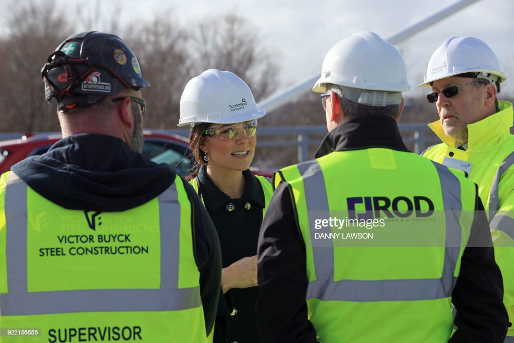 Britain's Catherine, Duchess of Cambridge, (C) talks to construction workers during a visit to the Northern Spire Bridge across the River Wear in Sunderland on February 21, 2018. The Duke and Duchess of Cambridge visited Sunderland to learn about the city's arts scene and engineering talent. Construction began on the three span cable-stayed structure bridge over the River Wear in Sunderland in May 2015. / AFP PHOTO / POOL / Danny Lawson