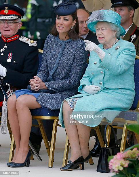 Britain's Catherine Duchess of Cambridge talks with Britain's Queen Elizabeth II as they watch a children's sports event during a visit to Vernon...