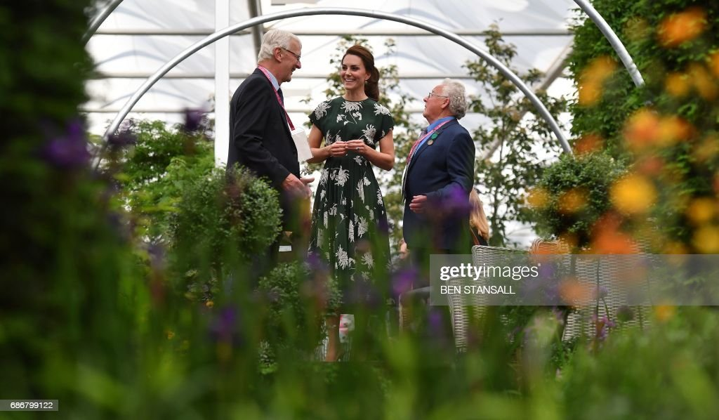 Britain's Catherine, Duchess of Cambridge (C) talks with exhibitors as she views a parterre at the Hillier garden display at the Chelsea Flower Show in London on May 22, 2017. The Chelsea flower show, held annually in the grounds of the Royal Hospital Chelsea, opens to the public this year from May 22. / AFP PHOTO / POOL AND AFP PHOTO / Ben STANSALL