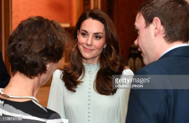 Britain's Catherine Duchess of Cambridge talks with guests as she attends a reception to mark the 50th Anniversary of the investiture of The Prince...