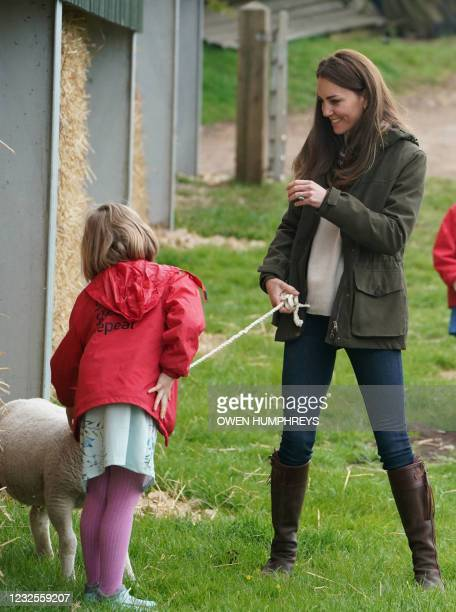 Britain's Catherine, Duchess of Cambridge talks with nine-year-old Clover Chapman, the daughter of farmer Stewart Chapman, as she strokes a lamb...
