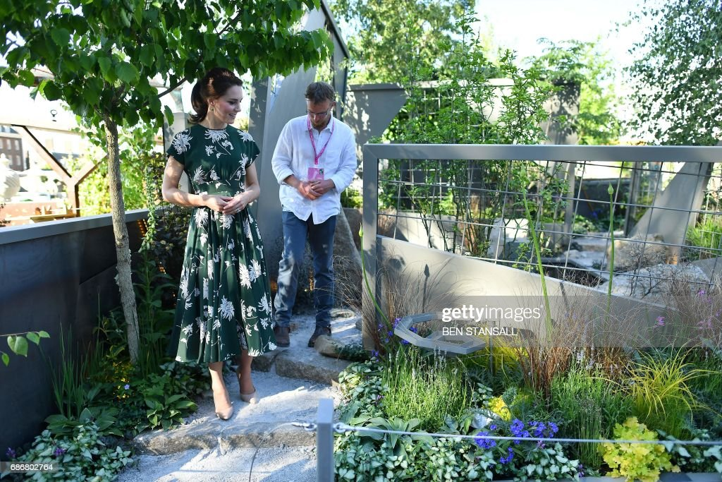 Britain's Catherine, Duchess of Cambridge (L) talks with Northern Irish designer Ian Price as she views his garden 'Mind Trap' at the Chelsea Flower Show in London on May 22, 2017. The Chelsea flower show, held annually in the grounds of the Royal Hospital Chelsea, opens to the public this year from May 22. / AFP PHOTO / POOL AND AFP PHOTO / Ben STANSALL