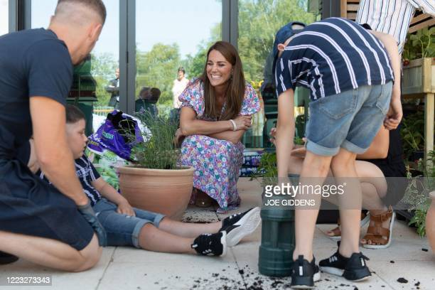 Britain's Catherine, Duchess of Cambridge, talks with Sonny Saunders , his father Jordan , sister Star, and brother Hudson during a visit to The Nook...