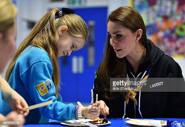 Britain's Catherine Duchess of Cambridge teaches a girl how to use chopsticks as she meets with children at the newly established 23rd Poplar Beaver...
