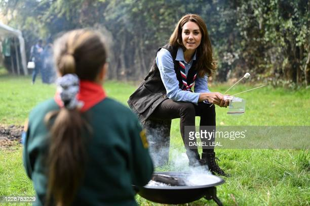 Britain's Catherine, Duchess of Cambridge, toasts marshmallows during her visit to a Scout Group in Northolt, northwest London on September 29 where...