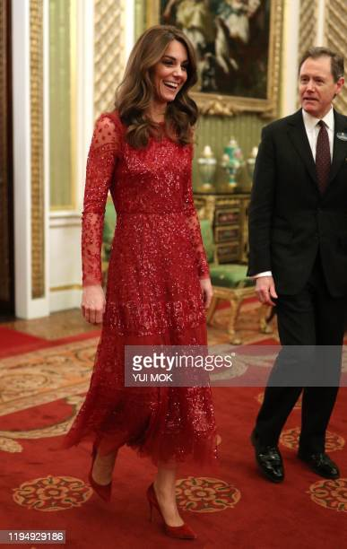 Britain's Catherine, Duchess of Cambridge walks through to the State Room with the Master of the Household at a reception for heads of State and...