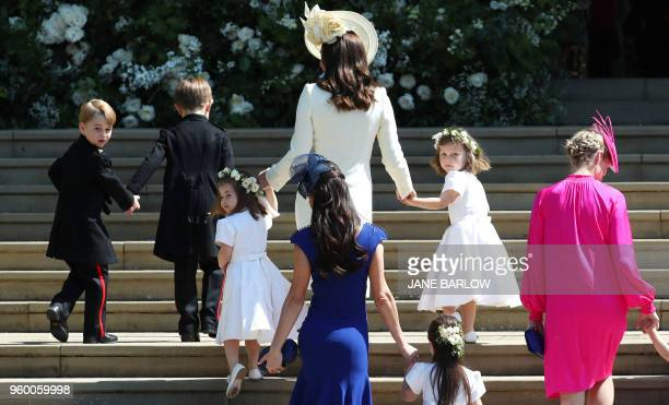 Britain's Catherine Duchess of Cambridge walks up the west steps with Prince George and Princess Charlotte and bridesmaids for the wedding ceremony...