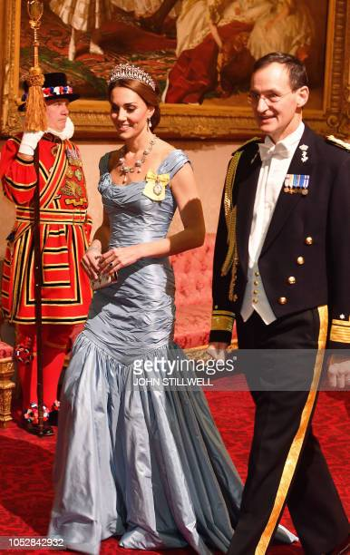Britain's Catherine Duchess of Cambridge walks with Rear Admiral Ludger Brummelaar as they attend a State Banquet in honour of King WillemAlexander...