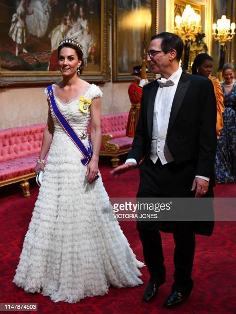 Britain's Catherine, Duchess of Cambridge walks with US Secretary of Treasury Steven Mnuchin as they arrive through the East Gallery during a State...
