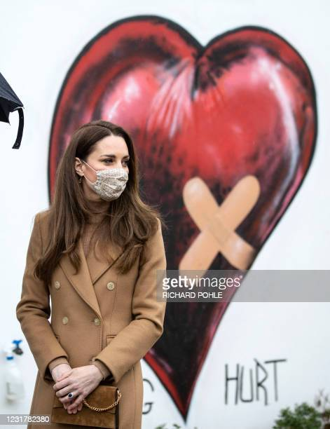 Britain's Catherine, Duchess of Cambridge, wearing a face covering due to Covid-19, meets with members of the ambulance service in the wellbeing...