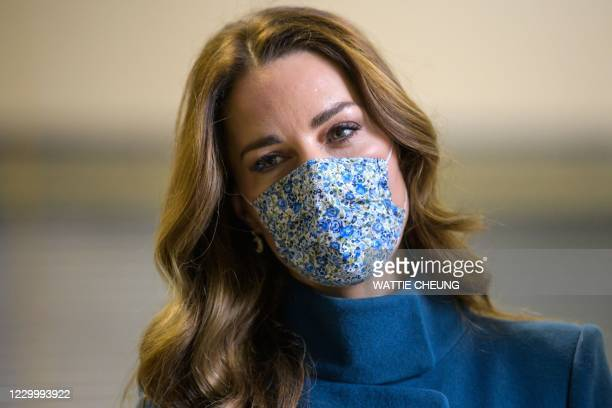 Britain's Catherine, Duchess of Cambridge wearing a protective face covering to combat the spread of the coronavirus, speaks with staff during a...