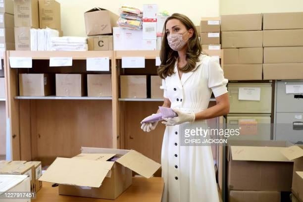Britain's Catherine, Duchess of Cambridge wears a face mask or covering and gloves due to the COVID-19 pandemic, helps unpack supplies during her...