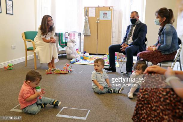 Britain's Catherine, Duchess of Cambridge wears a face mask or covering due to the COVID-19 pandemic, talks with family of Ali Wartty, Sahara...