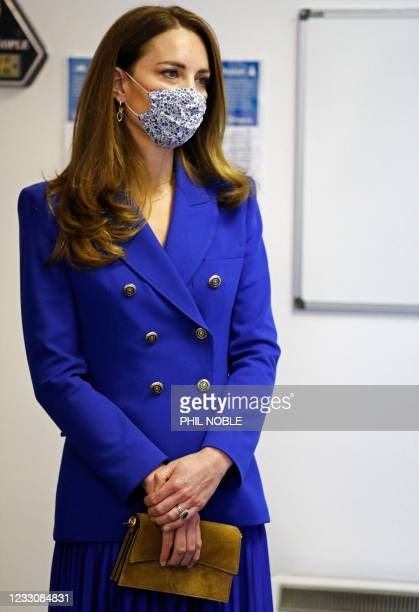 Britain's Catherine, Duchess of Cambridge wears a protective face covering to combat the spread of the coronavirus during a visit to Turning Point...