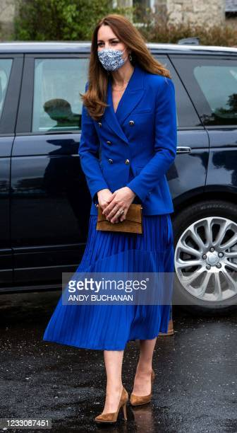 Britain's Catherine, Duchess of Cambridge, wears a protective face covering to combat the spread of the coronavirus, during a visit to a violence...