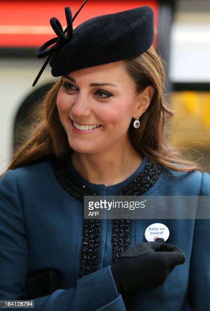Britain's Catherine Duchess of Cambridge wears a Transport For London badge that reads 'baby on board' given to her during a visit to Baker Street...