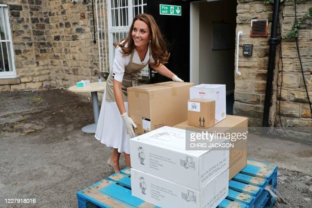 Britain's Catherine Duchess of Cambridge wears gloves and an apron as she helps to unpack supplies during her visit to Baby Basics baby bank in...