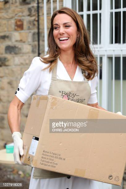 Britain's Catherine, Duchess of Cambridge wears gloves and an apron as she helps to unpack supplies during her visit to Baby Basics baby bank in...