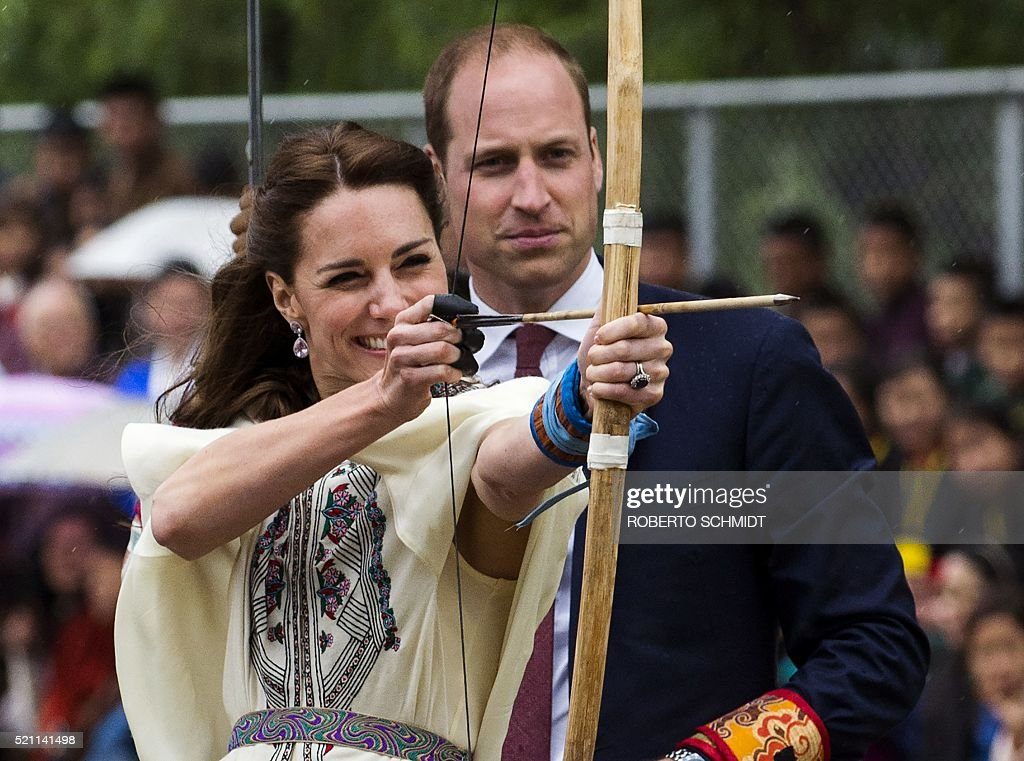 Britain's Catherine (L), the Duchess of Cambridge, fires an arrow as Prince William, Duke of Cambridge, looks on at the Changlingmethang National Archery ground in Thimphu during their visit to Bhutan on April 14, 2016. / AFP / ROBERTO