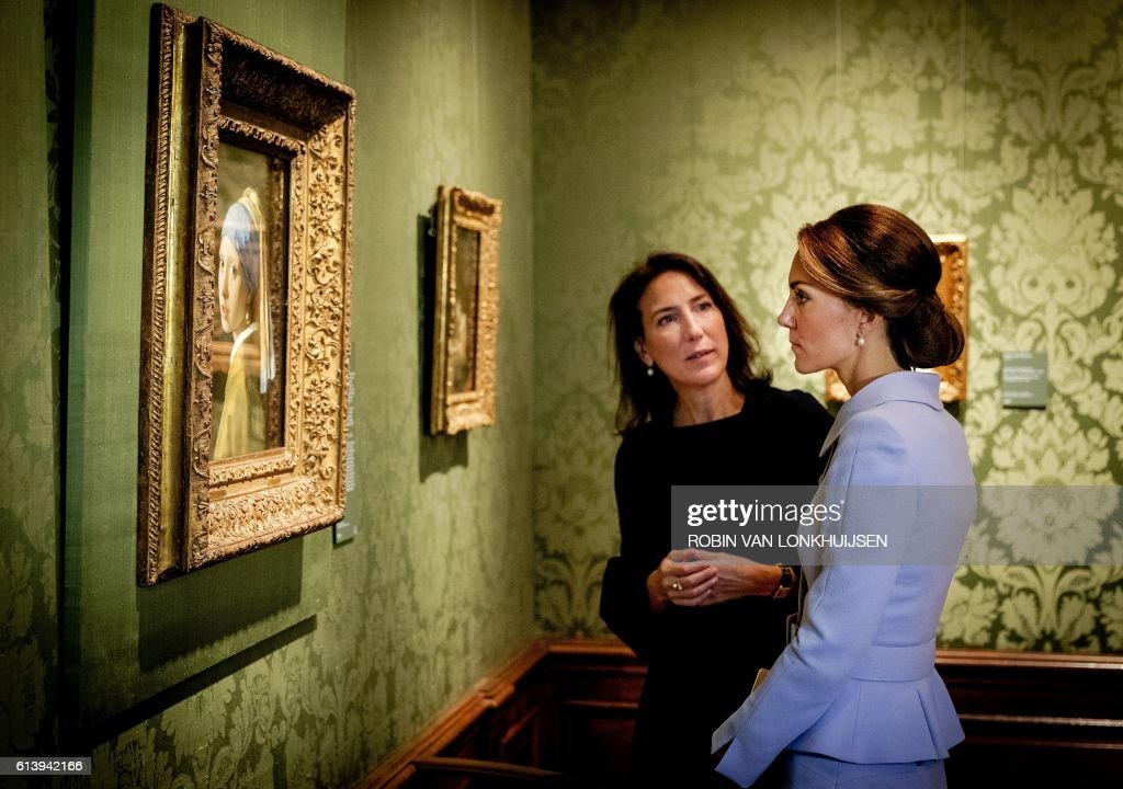 TOPSHOT - Britain's Catherine, the Duchess of Cambridge, looks at the famous Dutch 17th century painting 'Girl with a Pearl Earring' by Johannes Vermeer during her visit to the historic Mauritshuis Museum in The Hague's city centre, where she viewed 22 paintings by Dutch masters on loan from the British Royal Collection as part of a current exhibition on October 11, 2016. The Duchess of Cambridge, affectionally known as Kate, made her first solo official trip abroad with a day-long visit to The Netherlands, seen as part of a British charm offencive after the Brexit vote. / AFP PHOTO / ANP / Robin van Lonkhuijsen / RESTRICTED