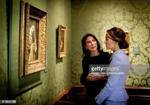 TOPSHOT Britain's Catherine the Duchess of Cambridge looks at the famous Dutch 17th century painting 'Girl with a Pearl Earring' by Johannes Vermeer...
