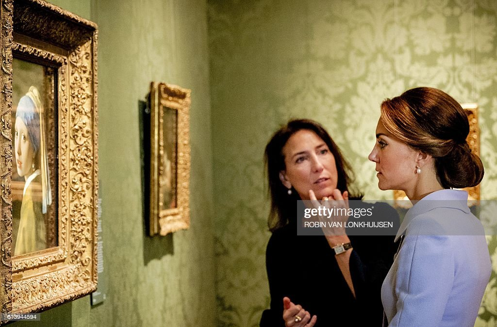 Britain's Catherine, the Duchess of Cambridge, looks at the famous Dutch 17th century painting 'Girl with a Pearl Earring' by Johannes Vermeer during her visit to the historic Mauritshuis Museum in The Hague's city centre, where she viewed 22 paintings by Dutch masters on loan from the British Royal Collection as part of a current exhibition on October 11, 2016. The Duchess of Cambridge, affectionally known as Kate, made her first solo official trip abroad with a day-long visit to The Netherlands, seen as part of a British charm offencive after the Brexit vote. / AFP / ANP / Robin van Lonkhuijsen / RESTRICTED