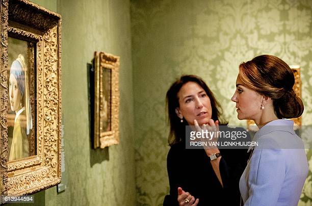 Britain's Catherine the Duchess of Cambridge looks at the famous Dutch 17th century painting 'Girl with a Pearl Earring' by Johannes Vermeer during...