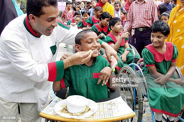 Britain's celebrity chef Tommy Miah helps a physically challenged child to eat as others look on in Saver some 20 kms north of Dhaka 26 February 2004...