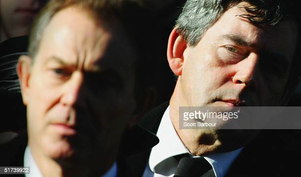 Britain's Chancellor Gordon Brown looks over the shoulder of Prime Minister Tony Blair as they stand for a two-minute silence at the annual...
