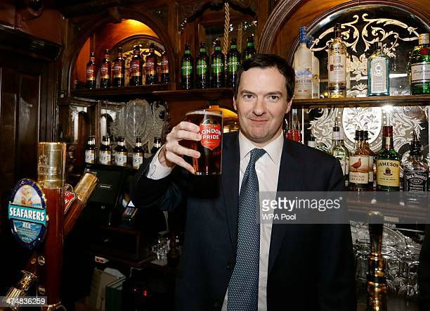 Britain's Chancellor of the Exchequer George Osborne holds a pint of beer during a visit to officially reopen The Red Lion pub following a major...
