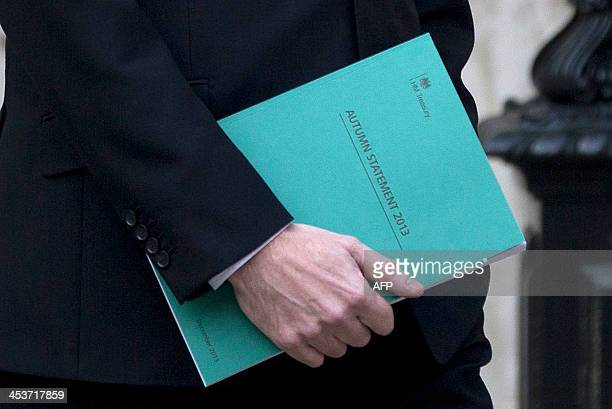 Britain's Chancellor of the Exchequer George Osborne holds his Autumn Statement document as he leaves the Treasury in London on December 5 2013 bound...