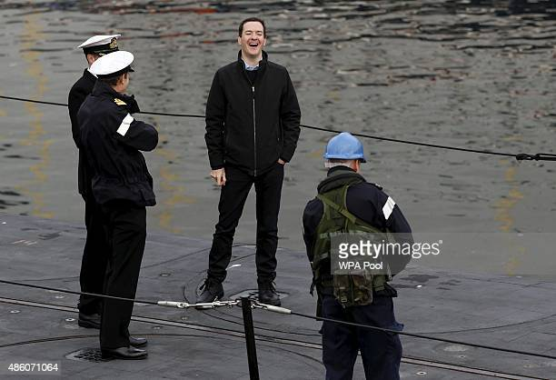 Britain's Chancellor of the Exchequer George Osborne laughs while talking to naval officers on a submarine during a visit to the Royal Navy's...