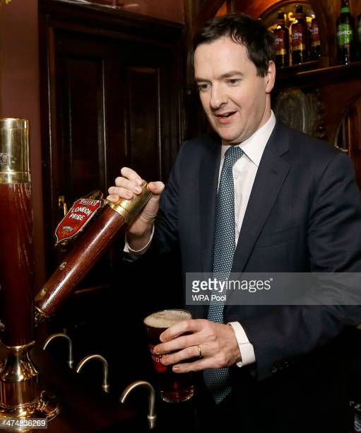 Britain's Chancellor of the Exchequer George Osborne pulls a pint of beer during a visit to officially reopen The Red Lion pub following a major...