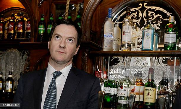 Britain's Chancellor of the Exchequer George Osborne stands behind the bar during a visit to officially reopen The Red Lion pub following a major...